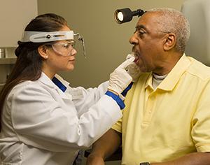 Врач обследует горло