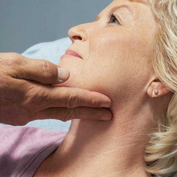 Врач осматривает челюсть больного