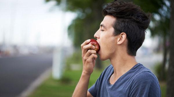 Человек ест яблоки